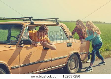 Young Hipster Friends On Road Trip On A Car