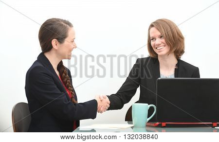 Business women in a job interview or business meeting shaking hands