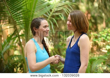 Two women expressing a truce or a greeting by shaking hands