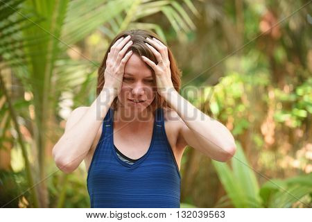 Young woman who is frustrated or worried with hands on head to express stress