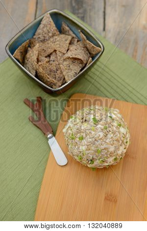 Cheese Ball with a Cheese Spreader for a festive party appetizer on rustic table