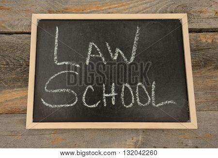 Law School written in chalk on a chalkboard on a rustic background