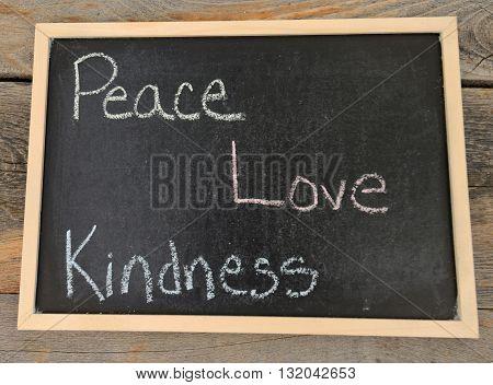 peace love kindness written in chalk on a chalkboard on a rustic background