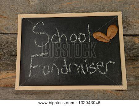 school fundraiser written in chalk on a chalkboard on a rustic background