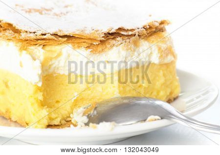 Close up of bitten vanilla cream cake isolates on white background