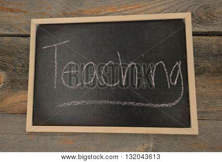 Teaching written in chalk on a chalkboard on a rustic background