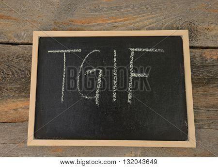 TGIF written in chalk on a chalkboard on a rustic background