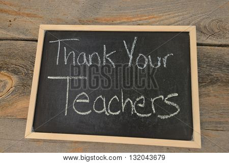 thank your teachers written in chalk on a chalkboard on a rustic background