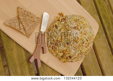 Gourmet Vegan Cheese Ball with a Cheese Spreader for a festive party appetizer on rustic table