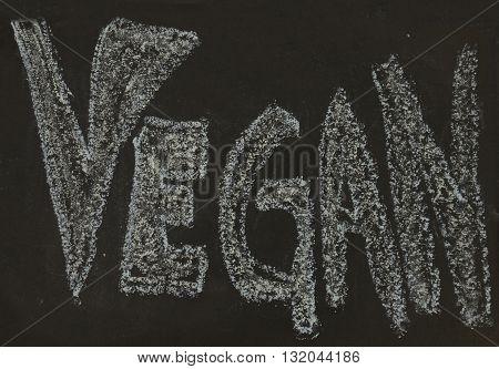 Vegan written in chalk on a chalkboard on a rustic background