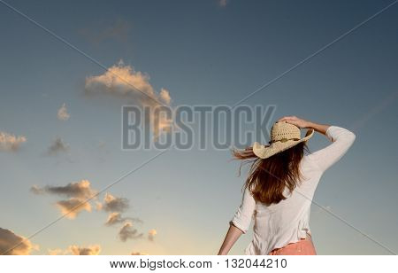 woman meditating and walking while alone with the sky as a background