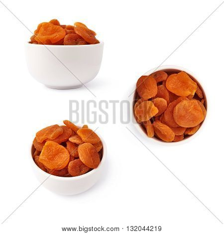 Dried orange apricots in ceramic bowl over isolated white background