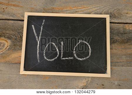 YOLO written in chalk on a chalkboard on a rustic background