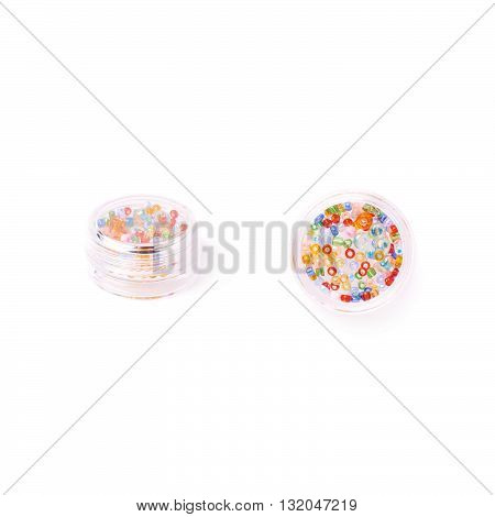Colorful beads in transparent round box over white isolated background
