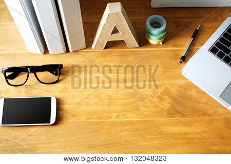 Desktop workspace with phone glasses laptop and binders