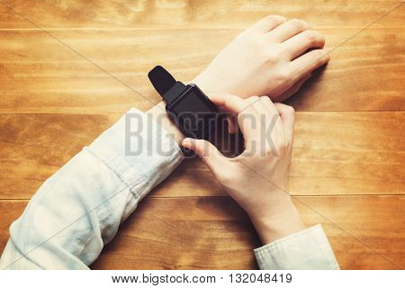 Person With A Smartwatch On A Wood Table