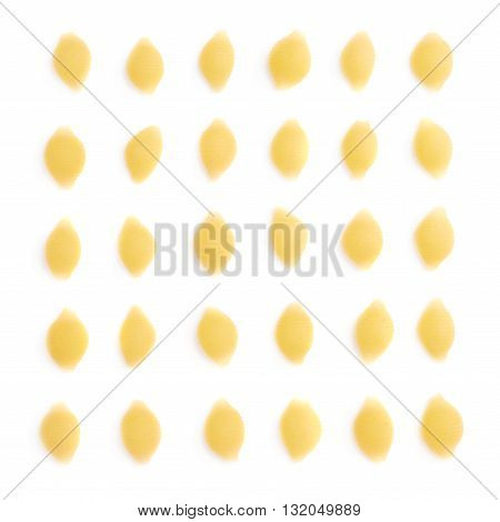Single pieces of dry conchiglie yellow pasta over isolated white background