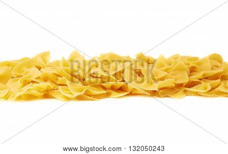 Line made of dry farfalle yellow pasta over isolated white background