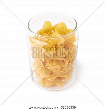 Glass jar filled with dry farfalle yellow pasta over isolated white background