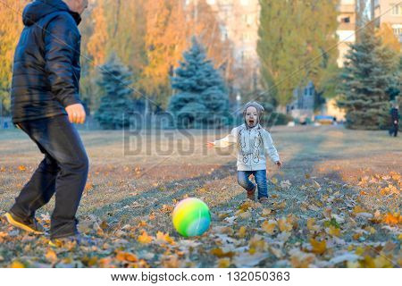 Happy father playing with his son at the ball in a park in autumn.