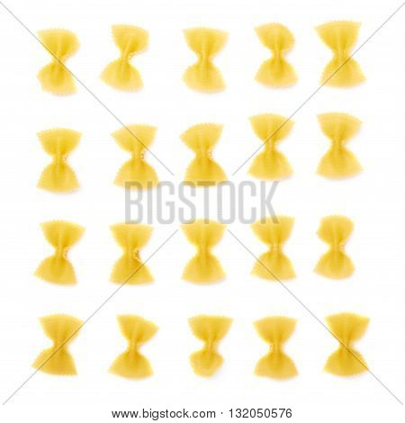 Single pieces of dry farfalle yellow pasta over isolated white background