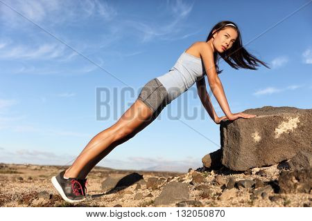 Strength training fitness woman working out core with angled pushups or planking on rock. Asian athlete exercising with bodyweight exercises for toned body. Workout in summer desert landscape.