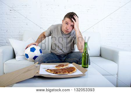 young supporter man with ball and pizza and beer bottle watching football game on television sitting at home couch in stress dejected and disappointed for failure or defeat