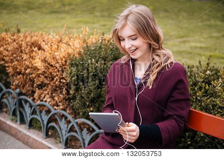 Smiling cute young woman sitting on bench and listening to music from tablet