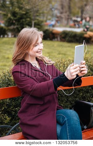 Happy charming young woman listening to music and making selfie using tablet in park