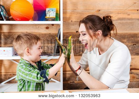 Happy young mother and her little son giving high five with painted hands in colorful paints