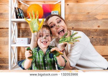 Cheerful excited mother and little son with painted hands in colorful paints having fun together