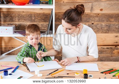Lovely young mother and little son painting together in art school
