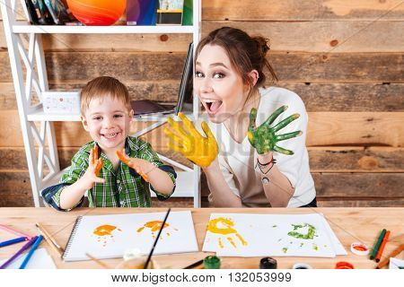 Smiling little boy and his mother having fun and showing hands painted in colorful paints