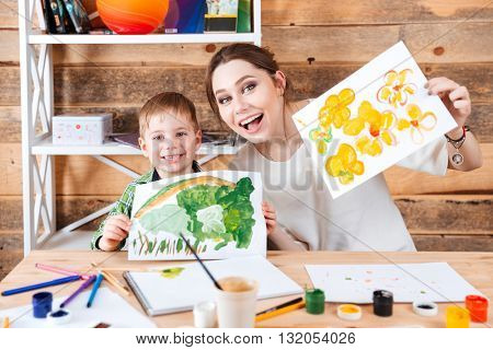 Happy cute little boy and his mother sitting and showing their paints