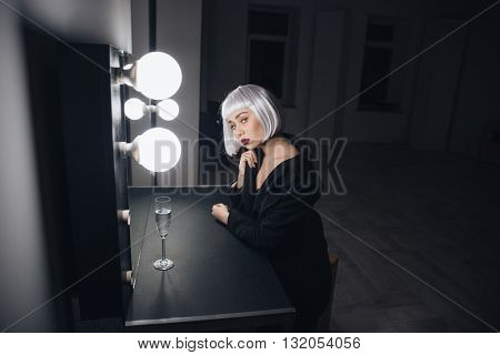 Sensual blonde young woman sitting near the mirror with glass of champagne