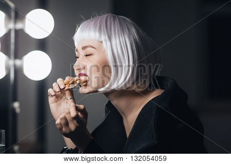 Funny cute young woman in blonde wig eating pizza in dressing room