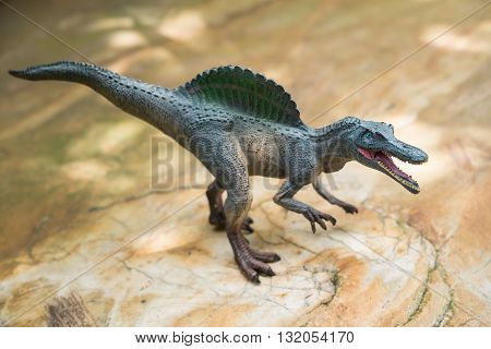 a grey spinosaurus toy standing on rock