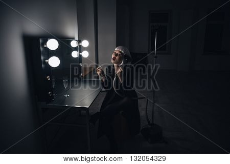 Crazy blonde young woman applying lipstick and playing with steamer in dressing room