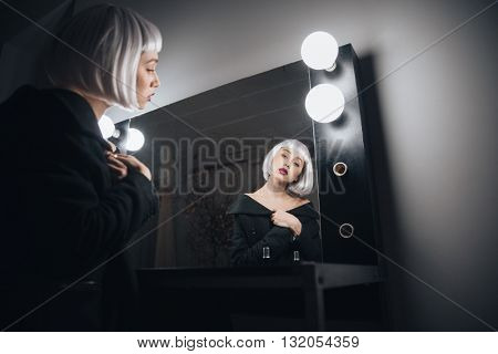 Attractive young woman in blonde wig sitting in front of the mirror in dressing room