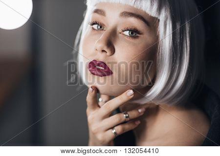 Closeup of beautiful blonde young woman touching her face