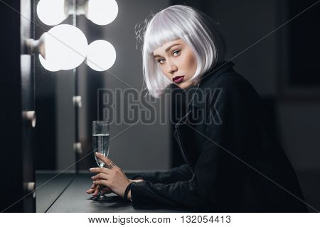 Portrait of attractive blonde young woman with glass of champaigne in dressing room