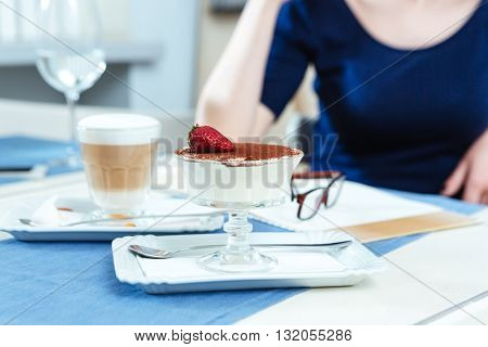 Closeup of sweet tasty dessert and coffee latte in glass for young woman sitting in cafe