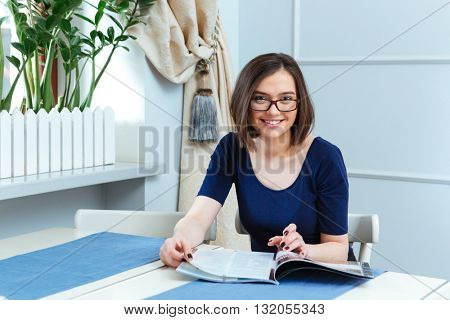 Cheerful beautiful young woman in glasses sitting and reading magazine in cafe