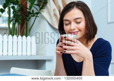 Smiling cute young woman drinking coffee latte in cafe