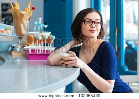 Happy attractive young woman in glasses drinking latte at bar counter in cafe