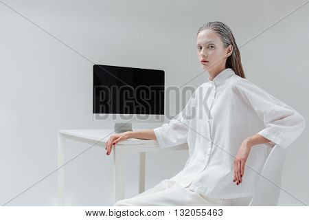 Beautiful fashion mystical woman sitting at the table with computer, pc