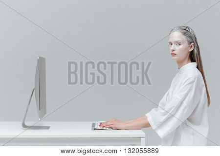 Fashion woman sitting at the desk with computer, pc over gray background