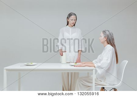 Two beautiful fashion women having a meal at the table and looking at each other over gray background