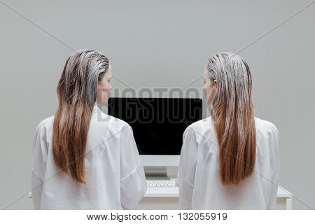 Two fashion mystic women looking at the blank monitor over gray background