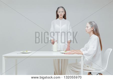 Two beautiful fashion girls having a meal at the table over gray background